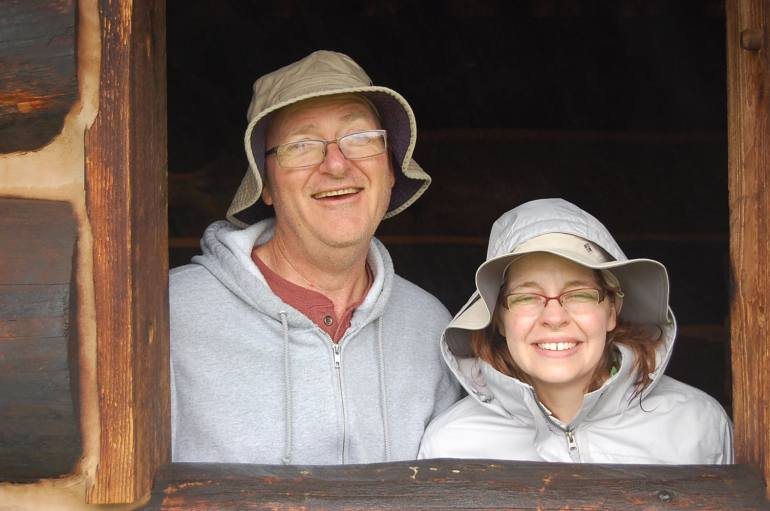The cute couple peers out from the cabin.
